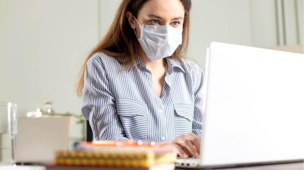 Professora de máscara durante a pandemia, dando aulas remotas em frente ao computador.