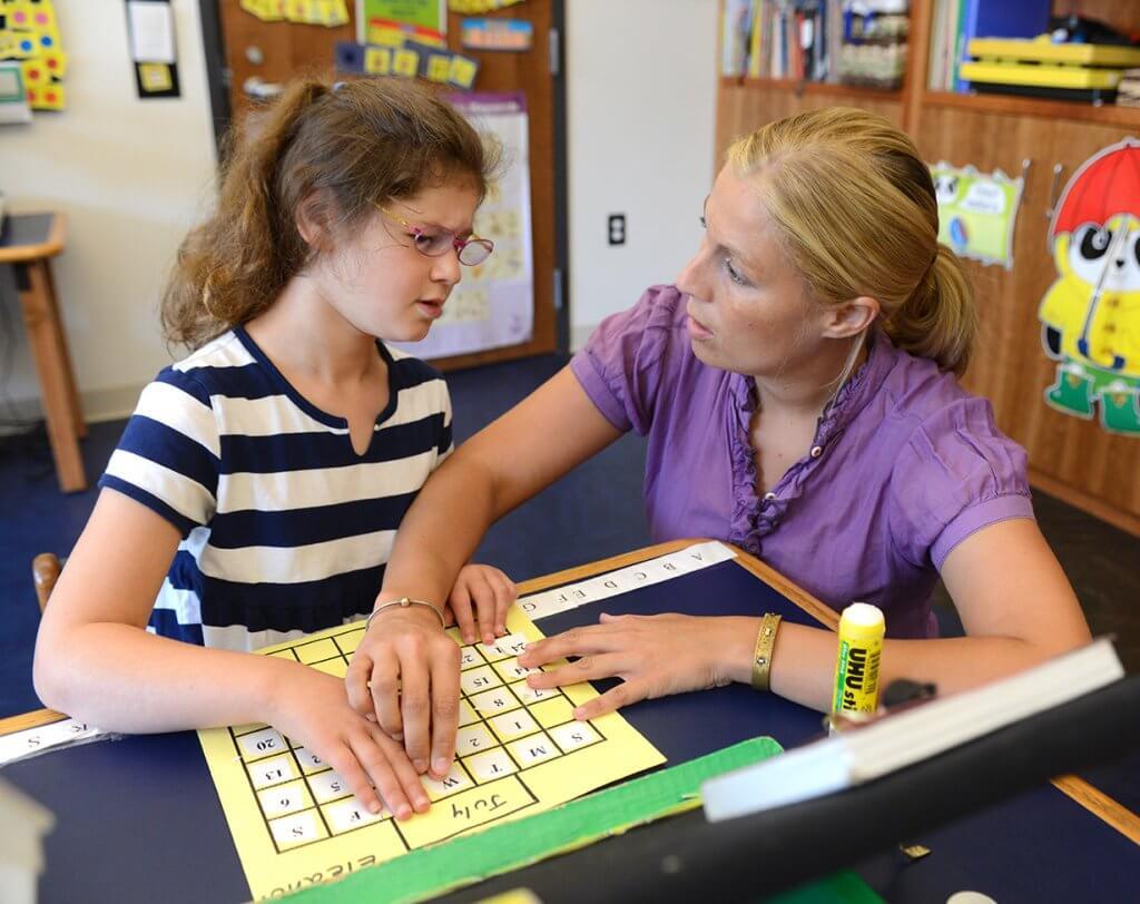 Professora atendendo aluna deficiente visual na escola